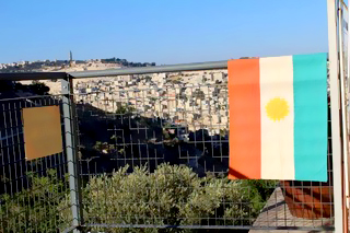 Kurdish flag, with the Mount of Olives in the background.